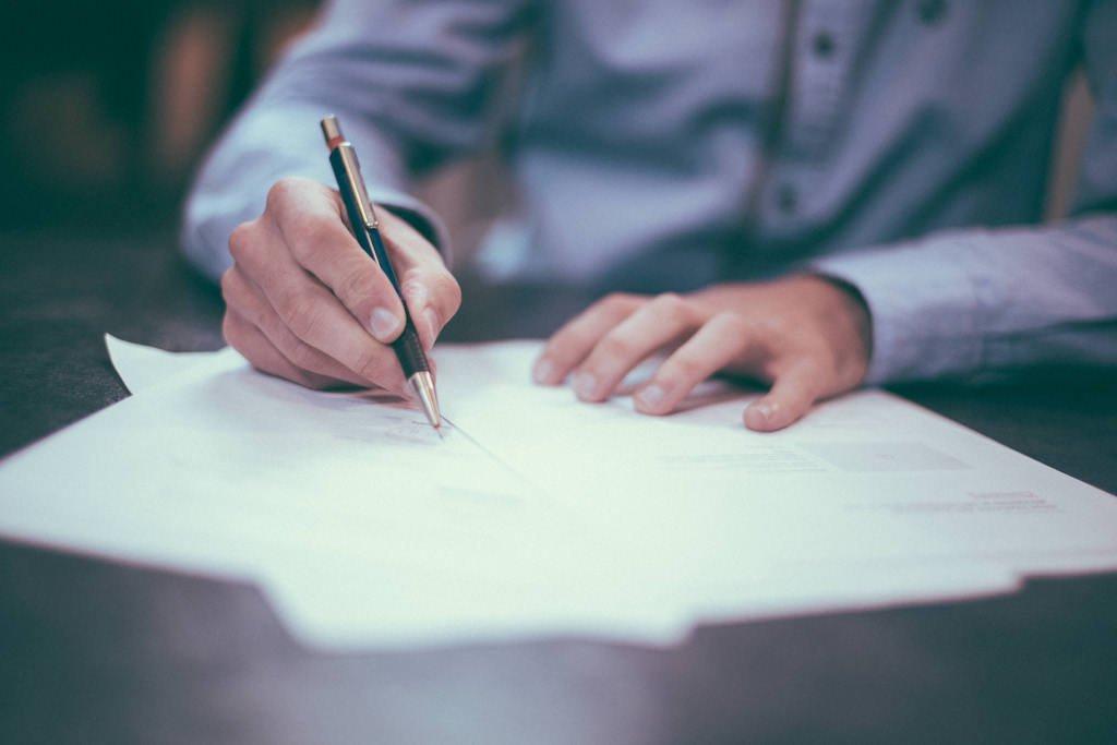 man signing car accident settlement paperwork in Pueblo, Manitiou Springs